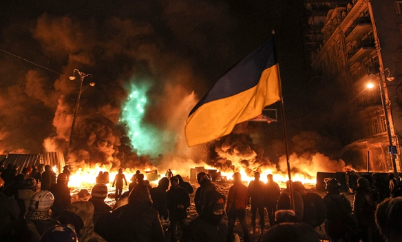 Pro-European integration protesters gather in front of burning tyres during clashes with riot police in Kiev