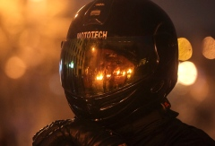 A pro-European integration protester looks on through a visor reflecting burning tyres at the site of clashes with riot police in Kiev